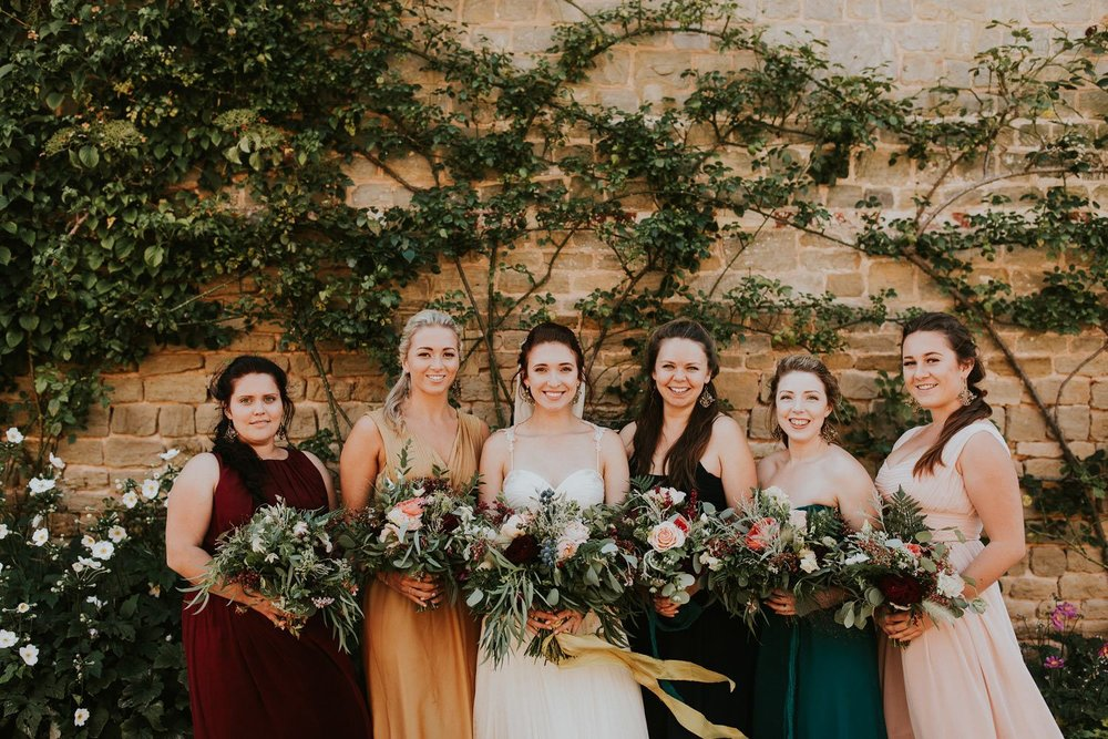 Bride and bridesmaids with rustic woodland bouquets in walled garden