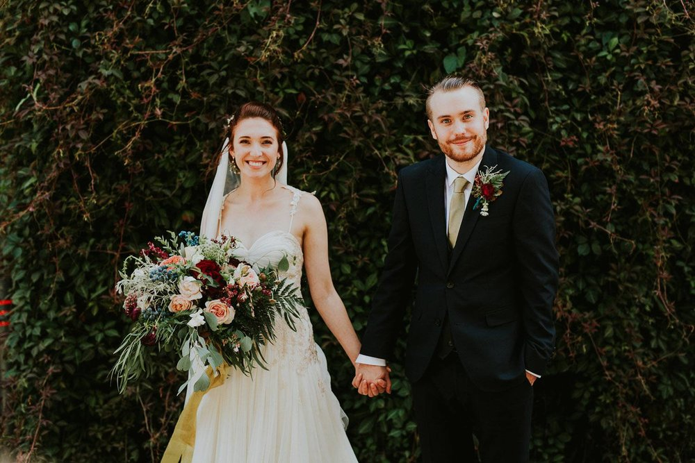 Woodland wedding couple with large rustic bouquet