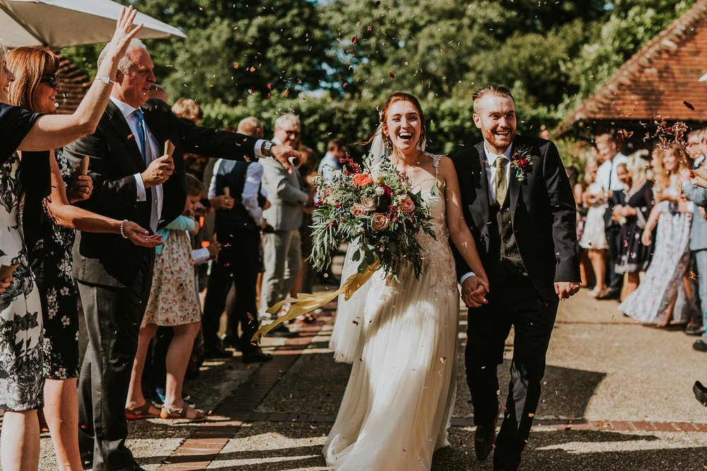 Wedding couple arrive at wedding reception with confetti