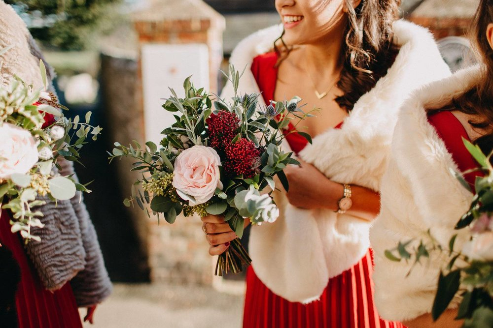 Bridesmaid with red dress, white fur shawl and rose bouquet