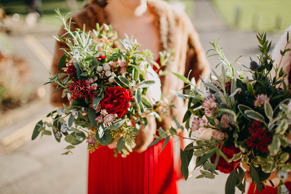 Bridesmaid wearing red dress holding winter bouquets