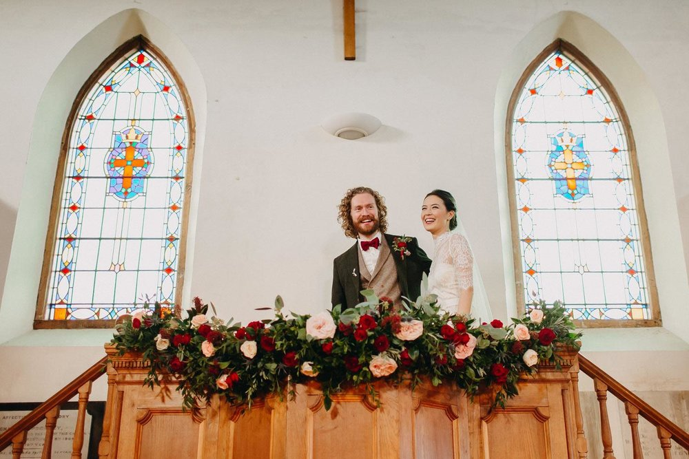Church ceremony altar flower garland with couple