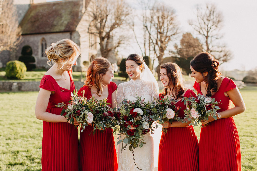 Winter bride with red bridesmaids and rose bouquets