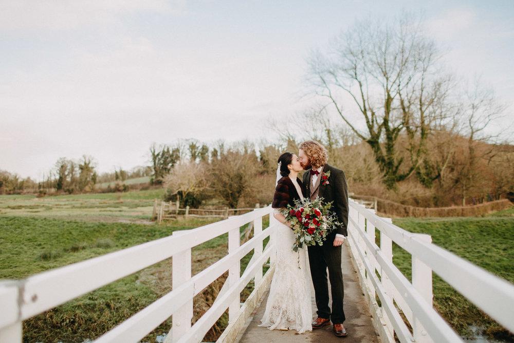 Winter wedding couple kissing on white wooden bridge