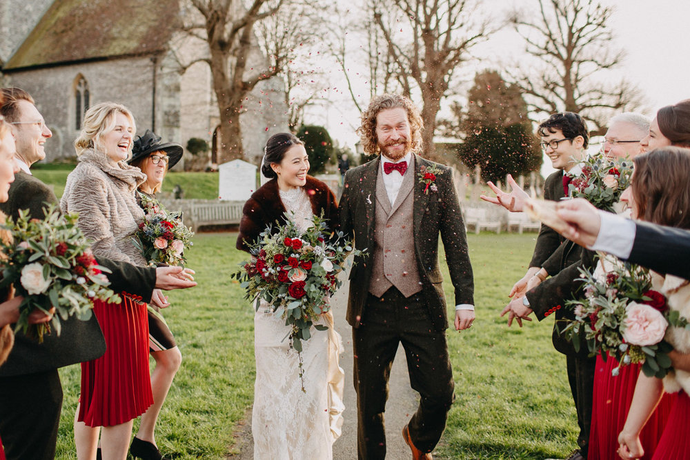 Winter wedding couple outside church with friends and family cheering