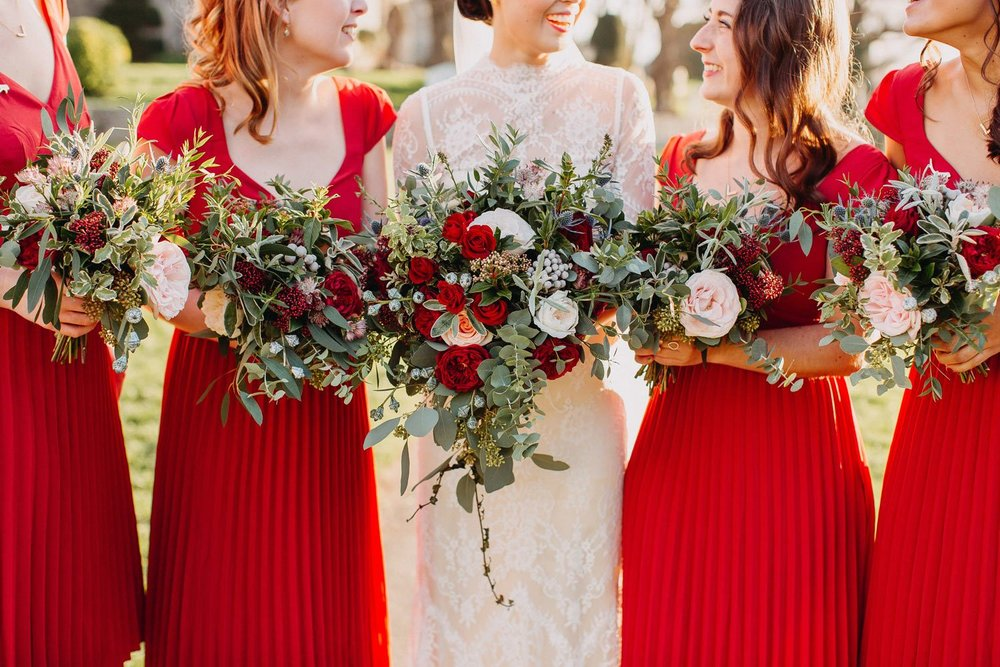 Bridesmaids in red dresses with winter rose bouquets