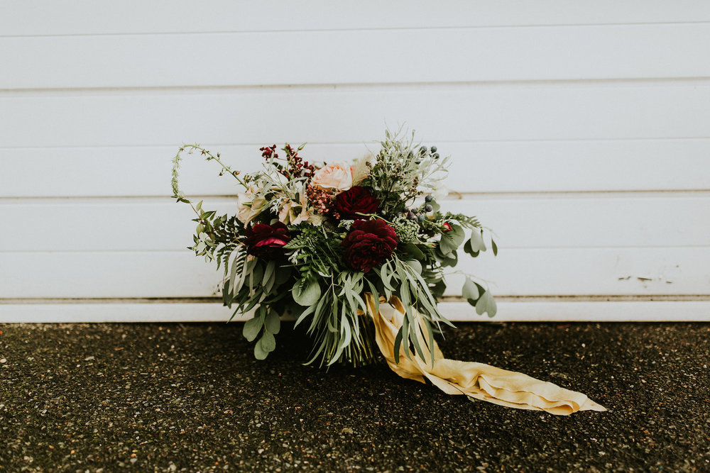 Rustic wedding bouquet by white wall