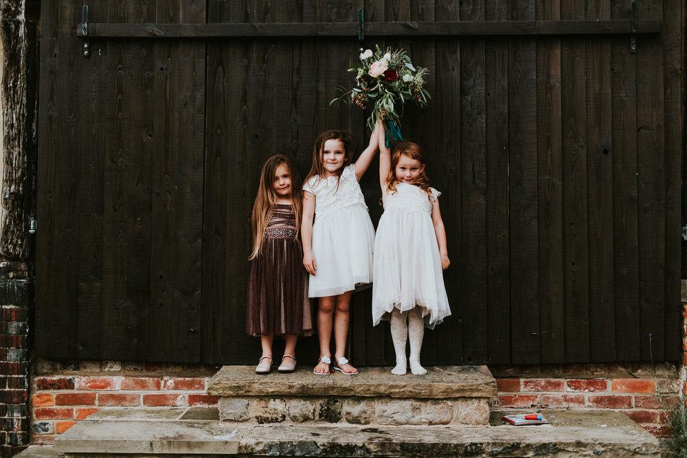 Flower girls posing with wedding bouquet