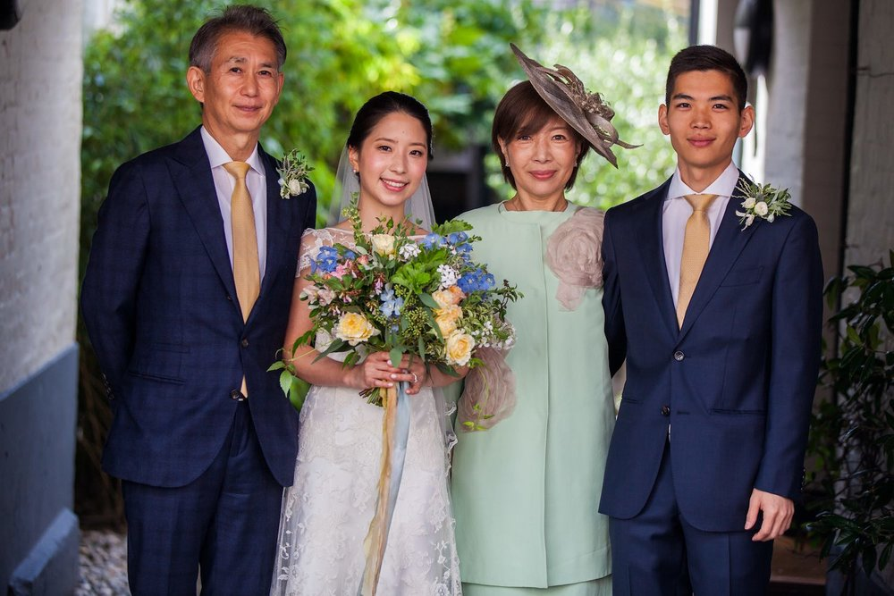 Japanese bride with family and holding bridal bouquet