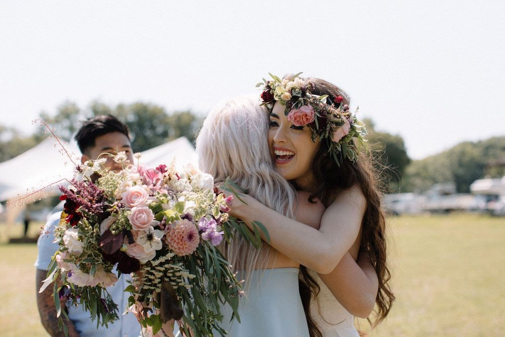 Bride greeting friends with bouquet in marquee