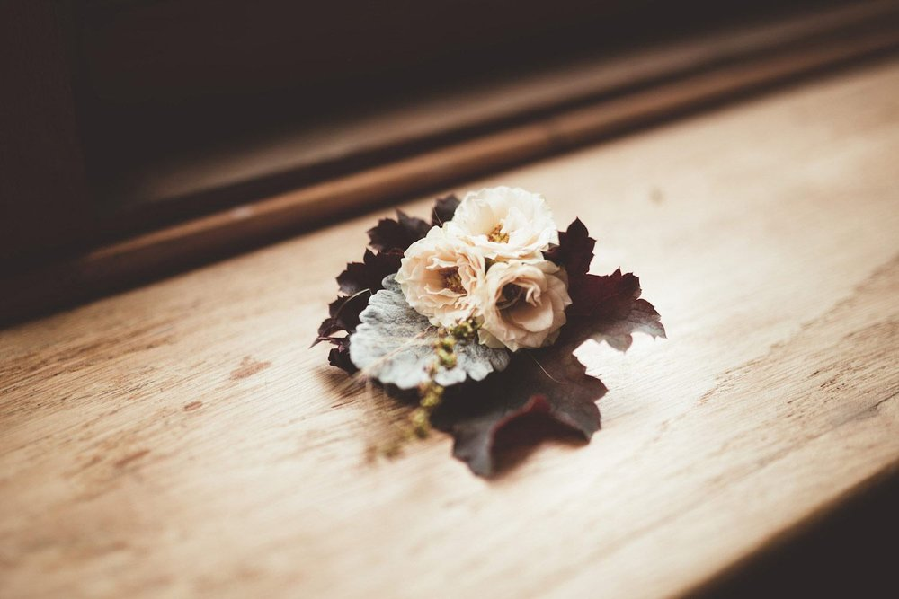 Buttonhole with red leaves and cream roses in window