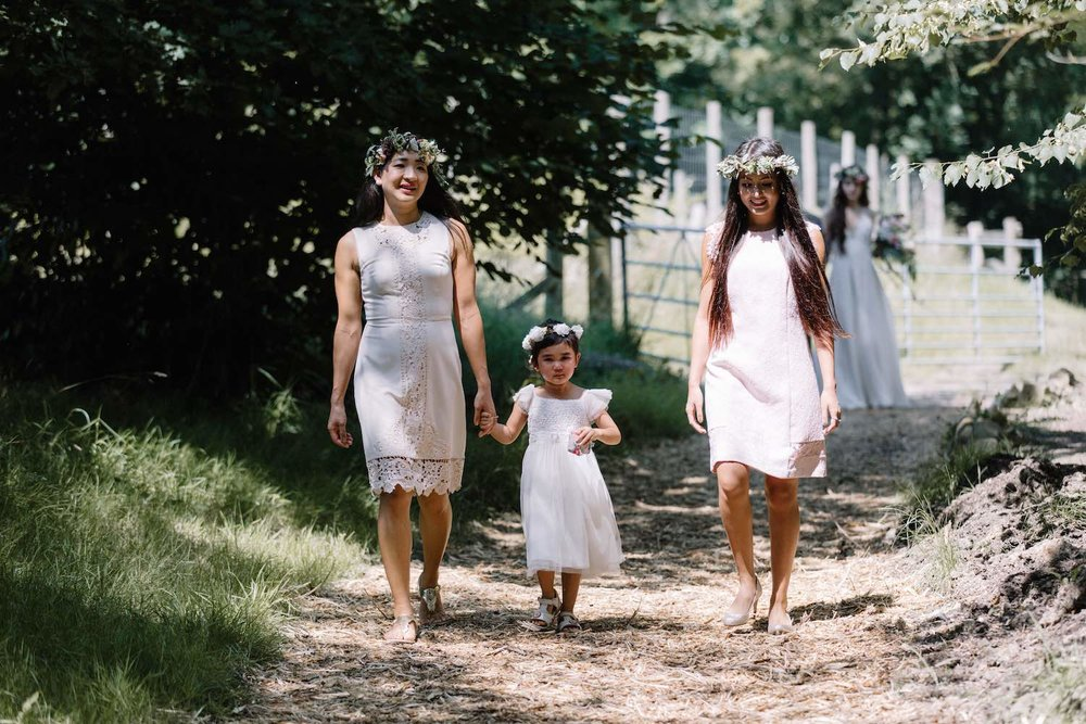 Bridesmaids and flower girl walking to woodland ceremony
