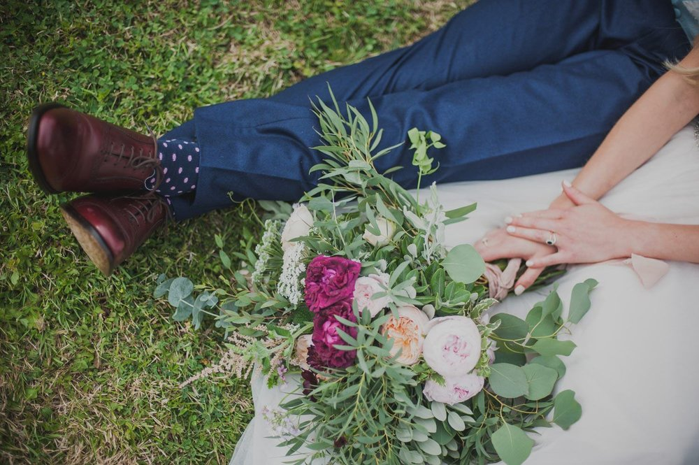 Bride and groom sitting in grass with flowers