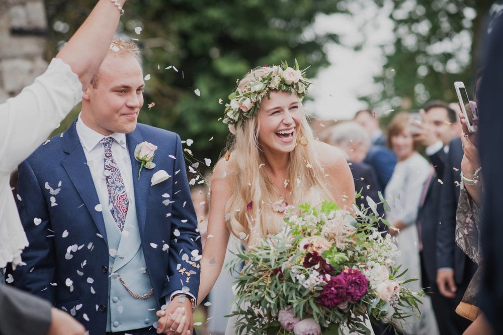 Bride and groom leaving church ceremony with flowers and confetti