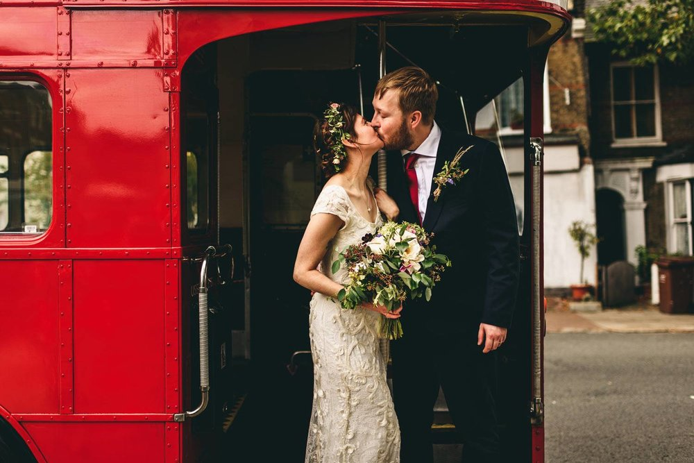 Bride and groom kissing on London bus with bridal bouquet