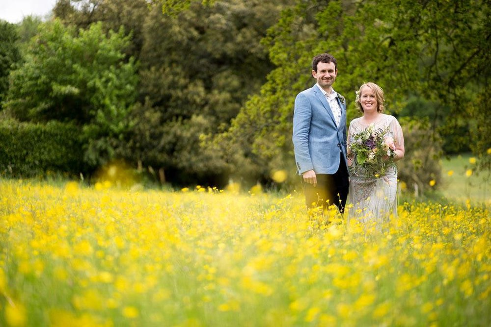 Bride and groom in yellow spring meadow