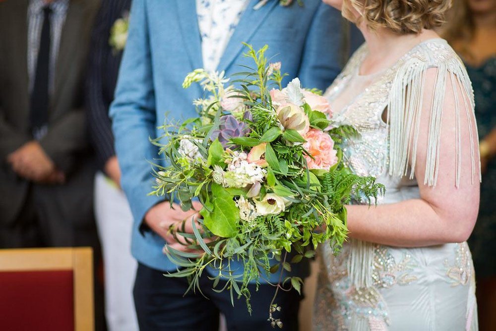 Bride and groom in wedding ceremony with wild bouquet