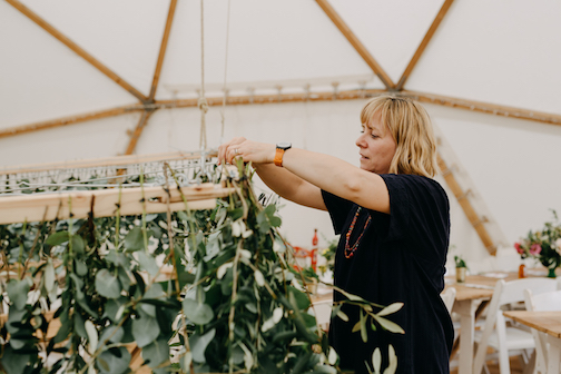 Bea arranging foliage chandelier in wedding marquee