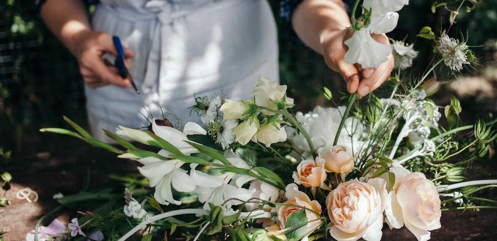 Bea arranging peach roses and white sweet peas in vase
