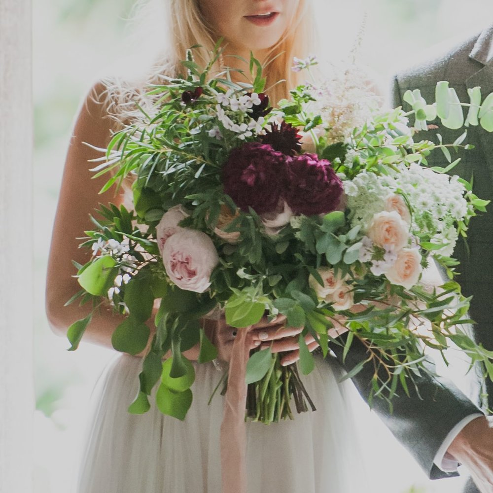 Bride holding vintage style bouquet with pale pink and burgundy garden roses