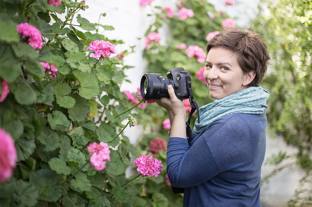 Eva Nemeth photographer with camera and flowers