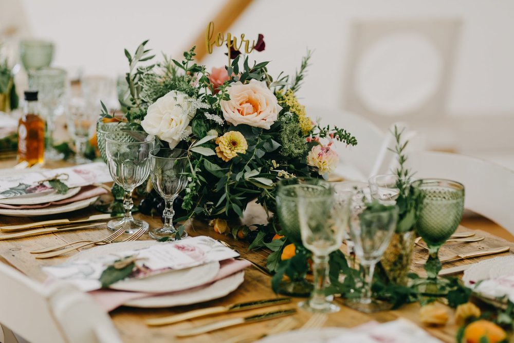 Wedding table set with rose and summer flowers centrepiece