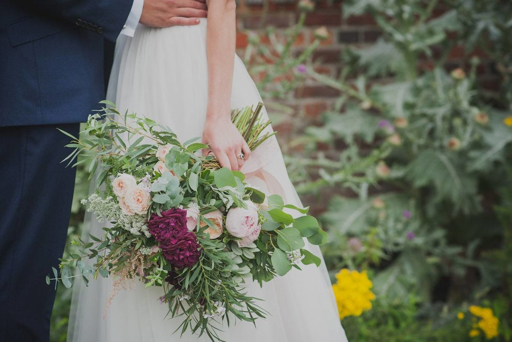 Country bride holding romantic bouquet with roses