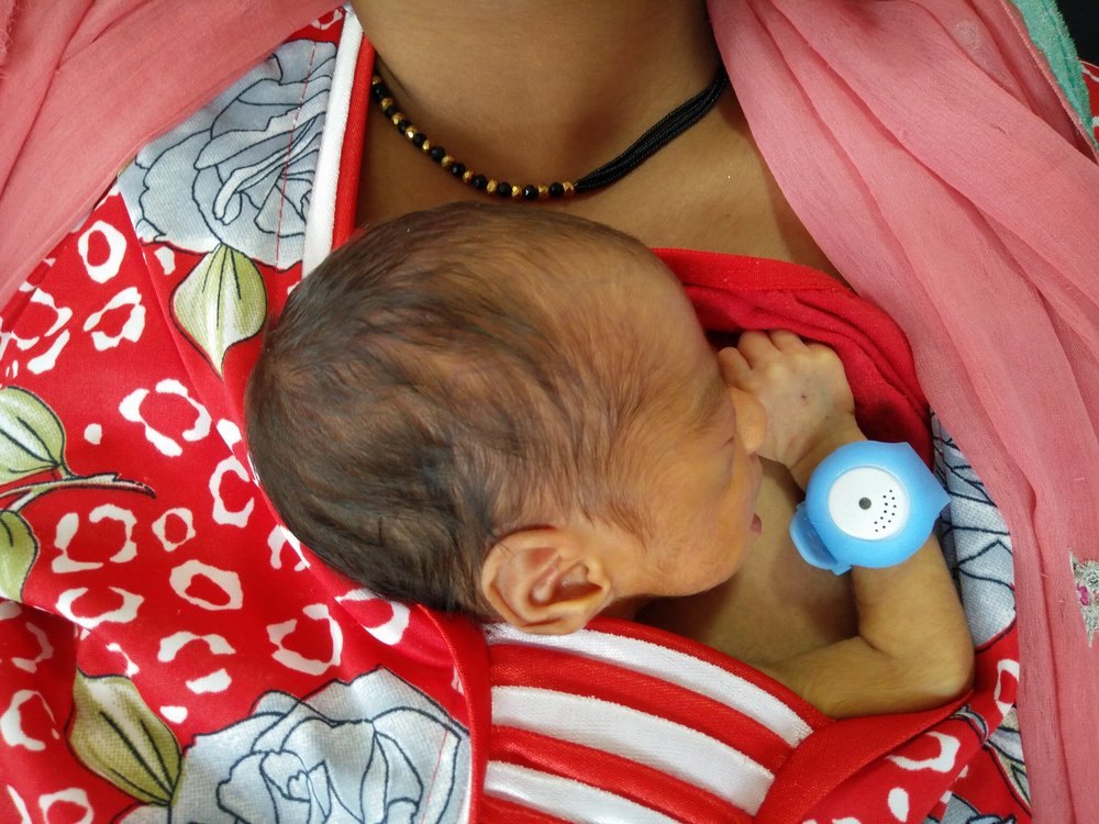 A baby in Rajasthan in KMC position wearing the BEMPU TempWatch