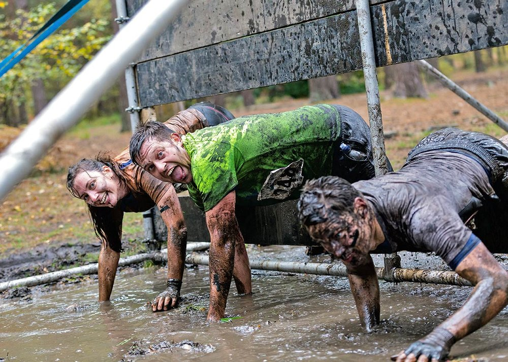 Clambering through the barriers covered in mud