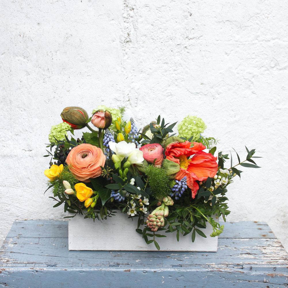 """Our spring flower trug arrangement with ranunculus and poppies is called """"Iduna"""" after the Norse goddess of spring and rejuvenation"""