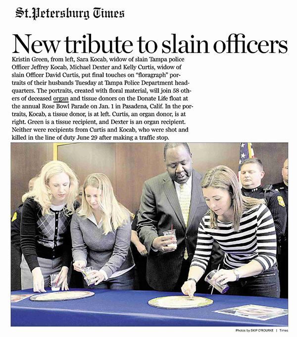 The widows of slain officers Jeffrey Kocab and David Curtis apply the finishing touches to their husbands' floraraph portraits at Tampa Police Department headquarters.