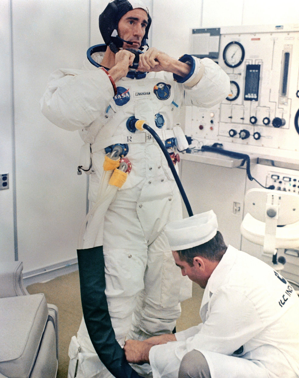 Walt Cunninghamadjusts his pressure siit with the help of a suit technician on launch morning. October 11, 1968. Photo Credit: NASA. Scan by Ed Hengeveld.