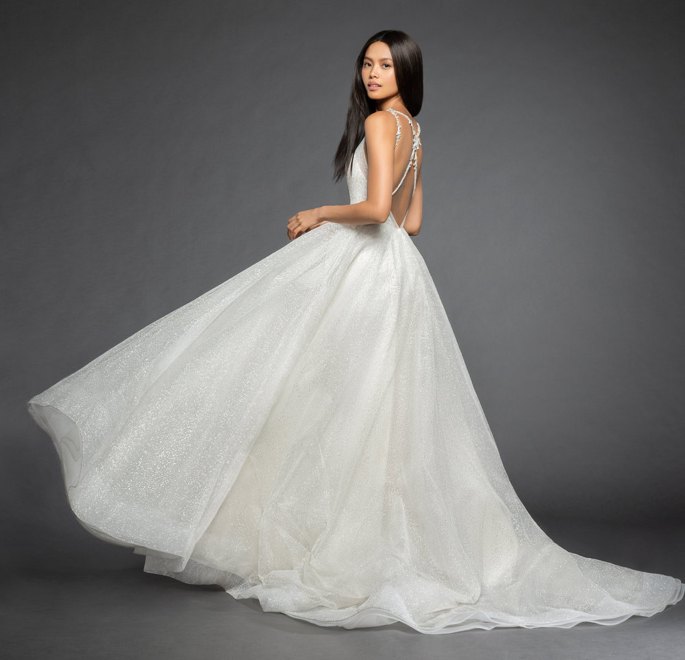 Y e s i    :  This stunning A-line skirt will keep you feeling like a modern day princess all celebration long! It incorporates a classic V-neck with a low, open back and rhinestone strap details.