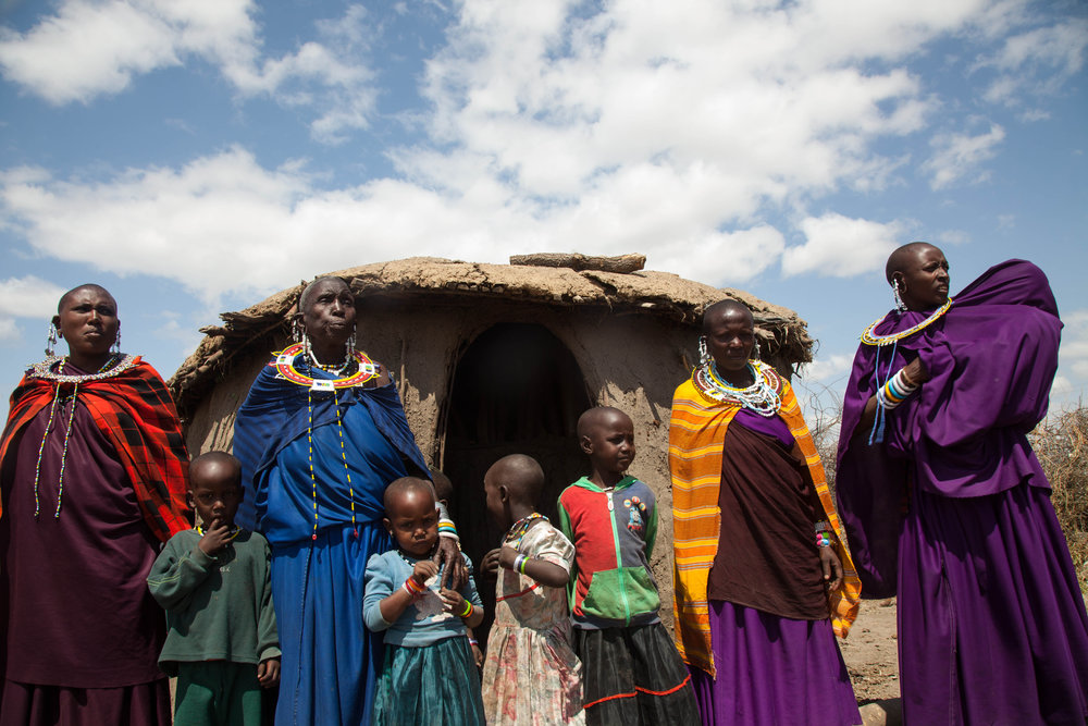 Nomadic Maasai women and children stand outside one of several bomas (or houses) made of mud and branches, where the Maasai live in a communal environment.