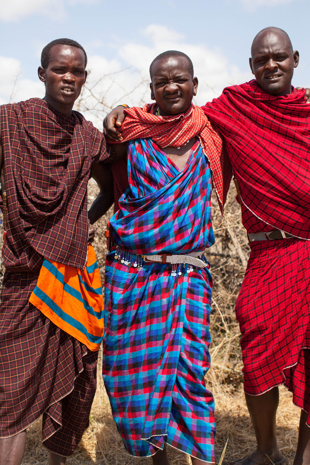 Maasai men in colorful woven fabrics at their home in the open bush in Tanzania, Africa.