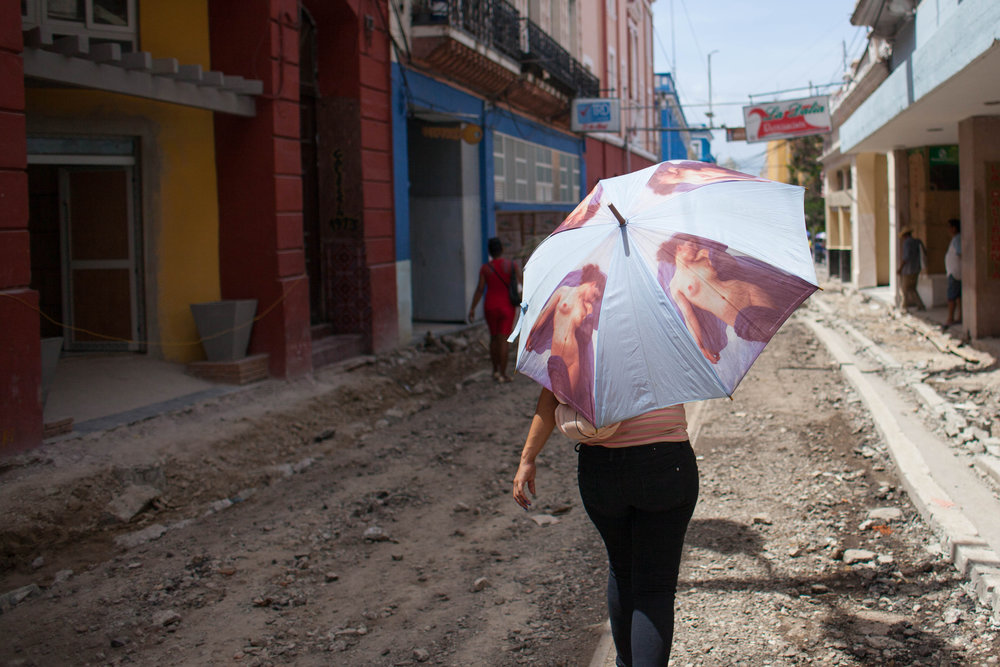 A woman walks down a crumbled street under construction for a walking path in Santiago de Cuba, Cuba.