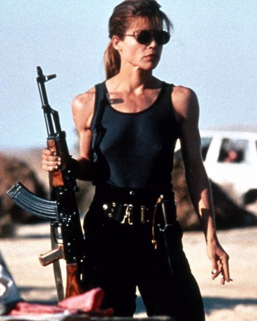 """NIKKI - Sarah Conner (The Terminator: 1984) – When mother Sarah Conner learns of Judgement Day (where machines unleash a nuclear holocaust on humanity), she becomes a badass warrior on a mission: to protect her only son John and prevent Judgement day from ever happening. I think Sarah is badass, because as a mom myself, I can completely relate to the lengths a mother will go to protect her children, doing whatever it takes to keep them safe. This is where the term """"Mama Bear"""" comes from; a mom will unleash holy hell on you if you go after or mess with her kids, and Sarah is badass for doing just that."""