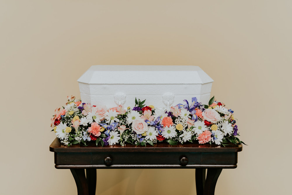 This stand-alone piece beautifully surrounds a 24-inch infant casket. The flowers completely encircle the casket when it is placed in the elevated space in the center of the flowers. This stand-alone piece beautifully surrounds a 24-inch infant casket. The flowers completely encircle the casket when it is placed in the elevated space in the center of the flowers.