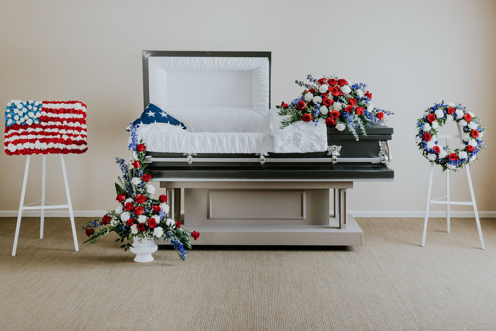 The Honor Collection features pieces inspired by the American flag, a patriotic spirit, and military service. Within the Honor Collection the American flag is used in three different settings with flowers to complement. First, the flag is folded and placed in the corner of the casket lid and pictured with a floral casket spray, flag and wreath easel arrangements and an urn arrangement surround the casket. Then, the flag is featured in a wood case next to a memorial urn arrangement. Finally, the flag is laid on the closed casket with a pedestal arrangement positioned behind the casket. The depiction of the flag using fresh cut flowers is designed using a custom form cut from wet foam to provide more longevity. The flowers used in this collection are blue delphinium, red roses, and carnations with complementing greenery.