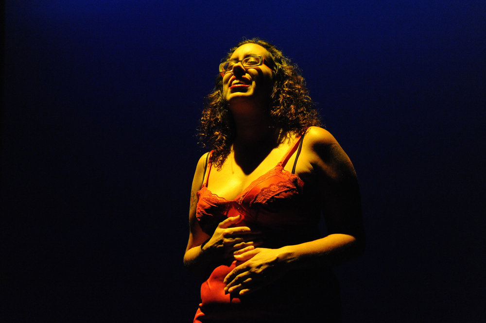Leah Lakshmi Piezpzna-Samarasinha, ©Richard Downing 2009. Image Description: A smiling Sri Lankan femme with curly brown hair, glasses, red lipstick and a red slip, her hands on her solar plexus and belly, illuminated against a black background.