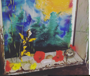 [Image Description: A multicolored altar made of a peeling wooden box with a mottled blue and green background, with orange and yellow flowers, a piece of quartz, a dancing figure, and what appears to be oat grass. It signifies sacred space and creative process.]