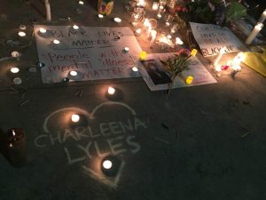 """Image taken by Lisa Ganser at a vigil for Charleena Lyles, in Seattle, WA, 6/18/17. Image description: a sidewalk at night with multiple votive candles and tall candles illuminating warm light in the darkness. Signs and flowers are spread throughout the sidewalk. A chalk drawing of a heart with 'Charleena Lyles' in the center. One white poster says: """"Black Lives Matter/People with Mental Illness Matter"""""""