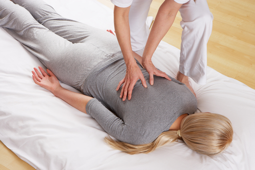 shiatsu massage therapist giving back massage in Bristol
