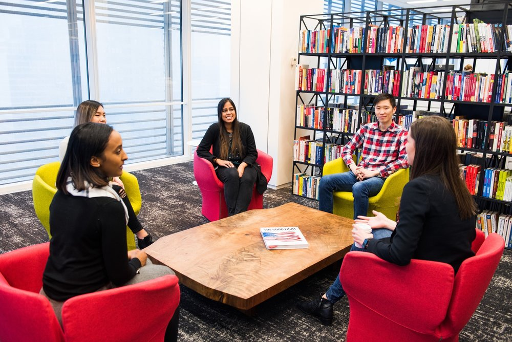 Five Liquidnet employees socializing in the fintech company library