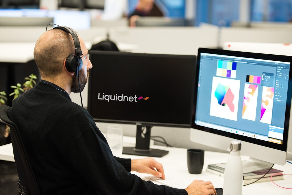 Liquidnet designer with headphones working on financial technology solutions