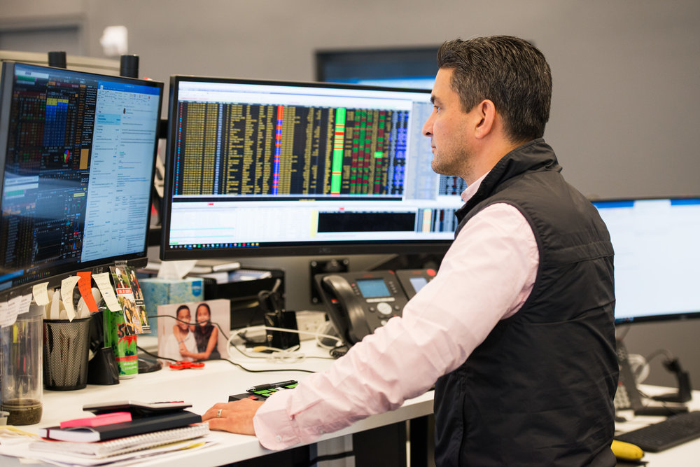 Liquidnet employee at two-monitor standing desk distilling real time market intelligence into trade analytics