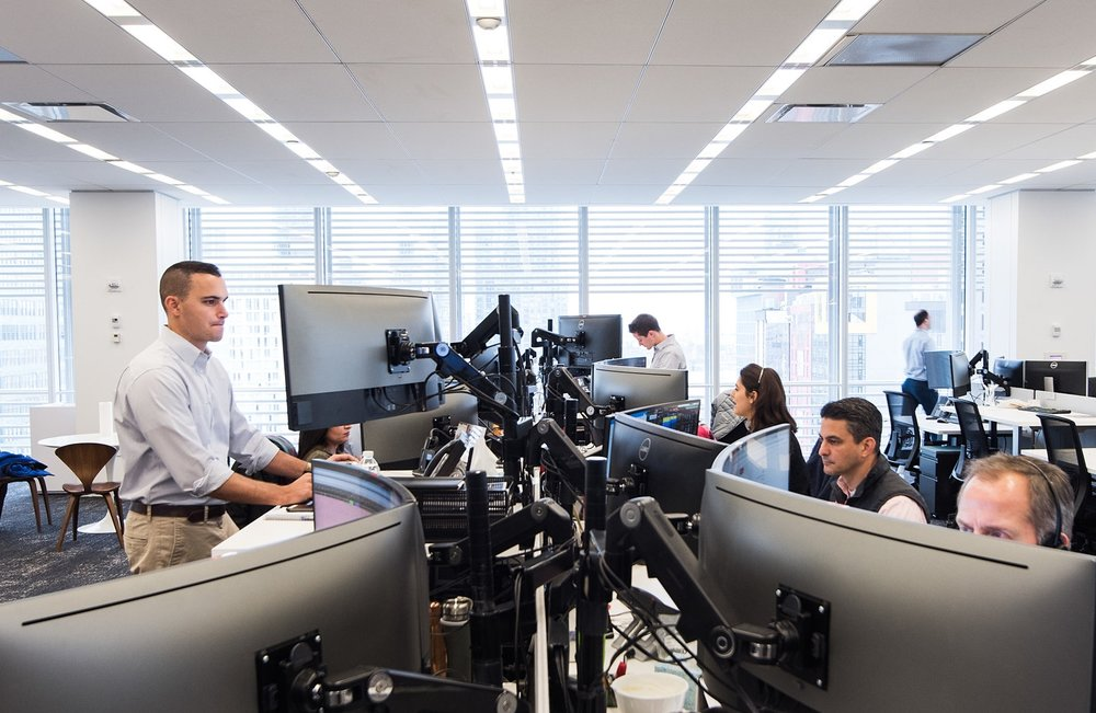Liquidnet employees work on information security initiatives at bank of workstations with curved monitors