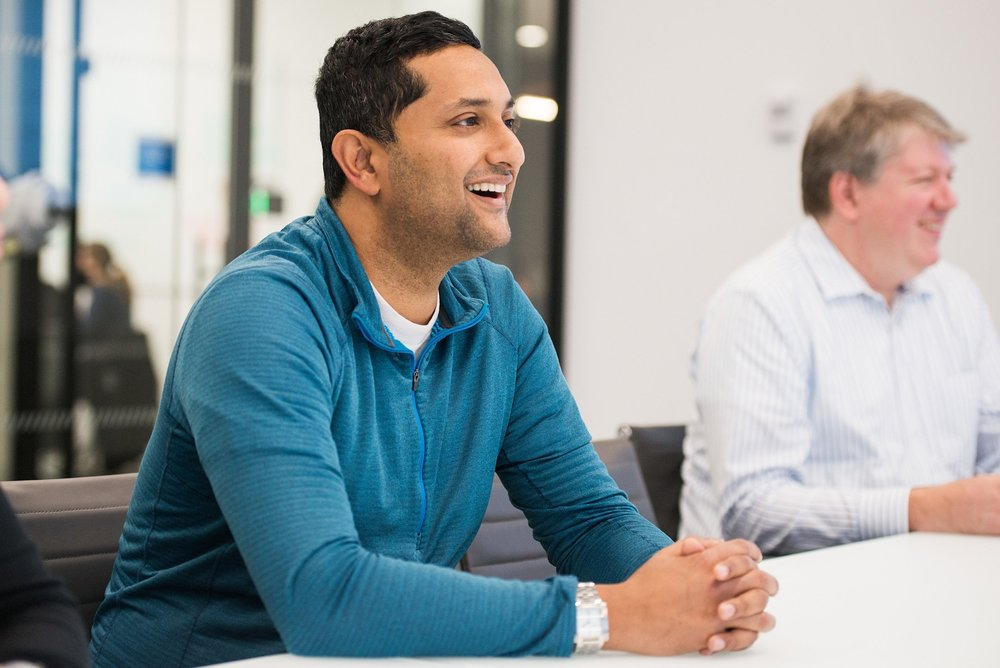 Liquidnet employee sitting and smiling at conference table