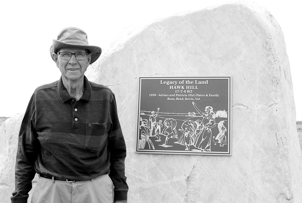 Adrian Paton beside the plaque he and his family erected on Hawk Hill, located southwest of the farmyard where he lived for most of his life.