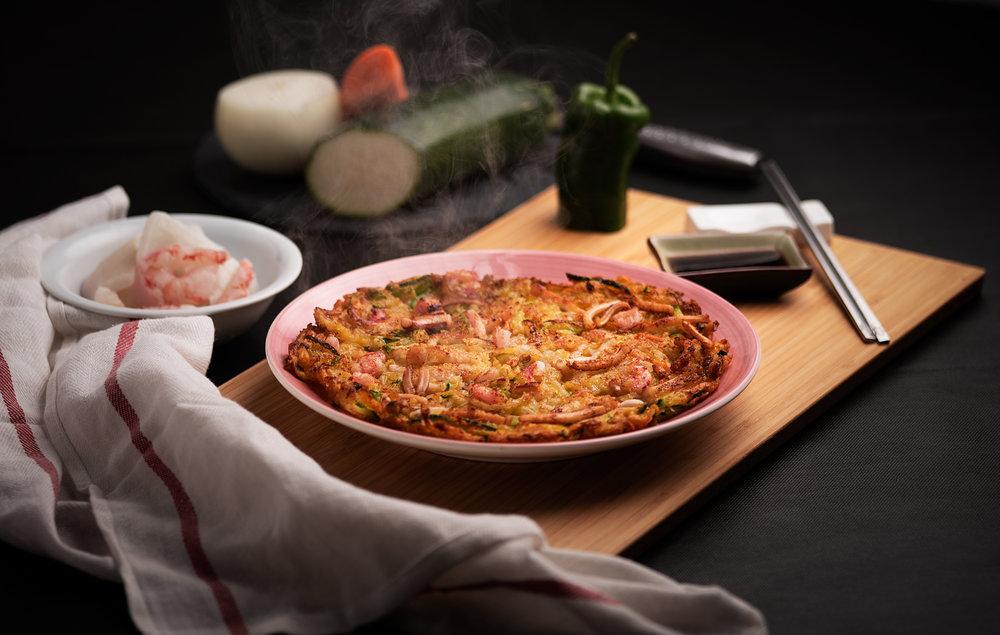 Jemulyon - Tortilla de mariscos y verduras.Una de los variados tipos de tortillas tradicionales coreanas.Tortilla recien hecha crujiente por fuera y suave por dentro con un relleno completo de calamares, gambas y verduras variadas. Servida con salsa de soja.Una tortilla como nunca habrás probado.7.50€